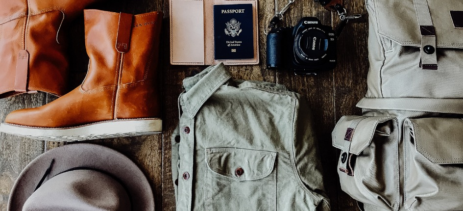 Boots, a hat, a camera, a passport, shirt, camera, and backpack laid out on a rustic wooden table