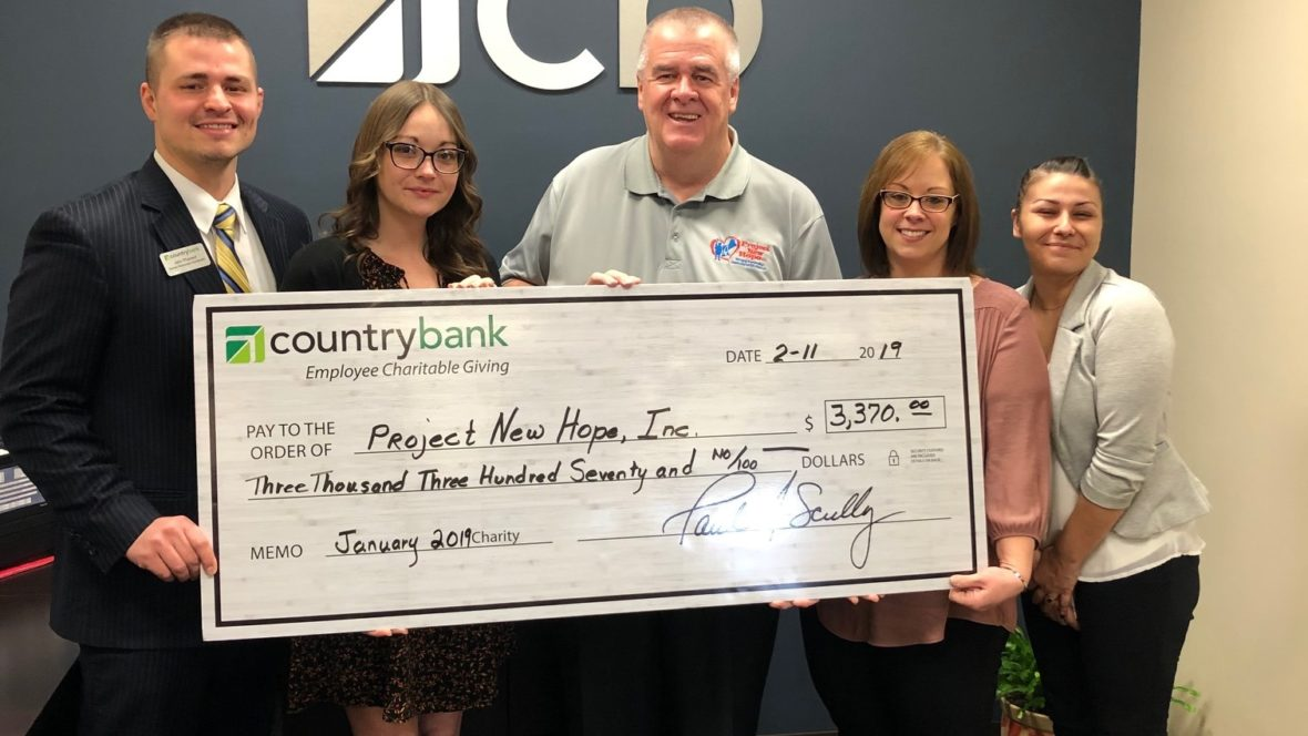 Group photo of Country Bank staff and a representative from Project New Hope for a check presentation.