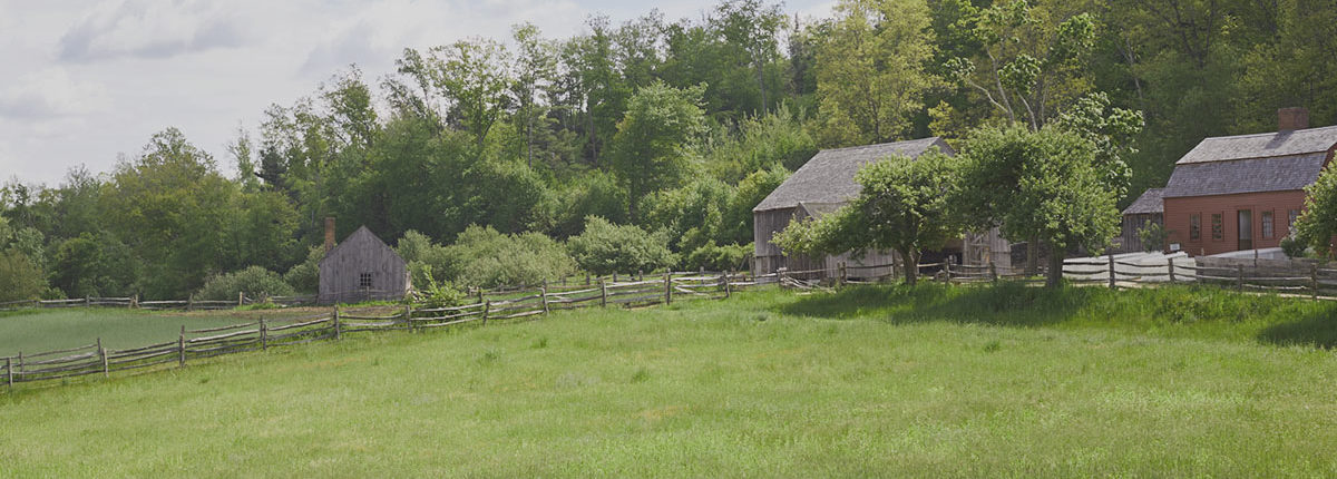 A rustic setting with buildings and fields