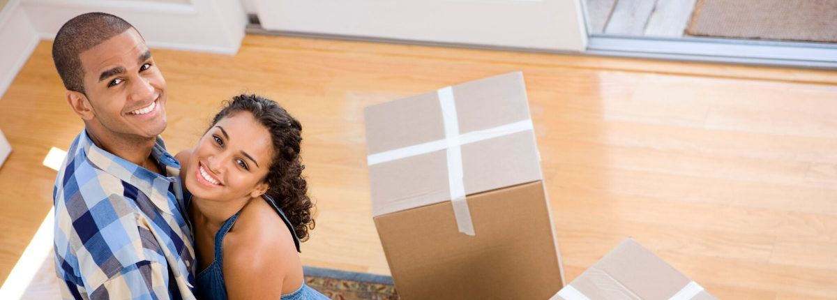 Couple smiling with boxes in a new home