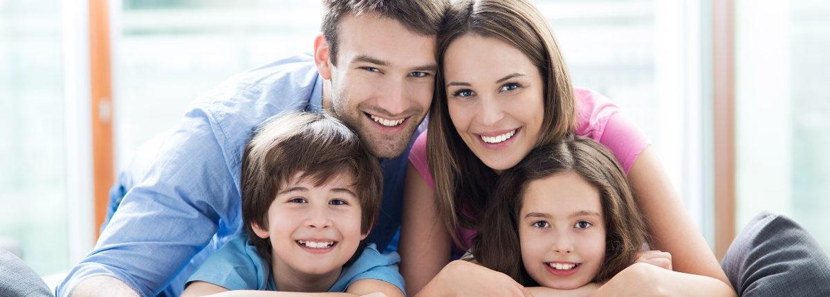 Family of four huddled together smiling
