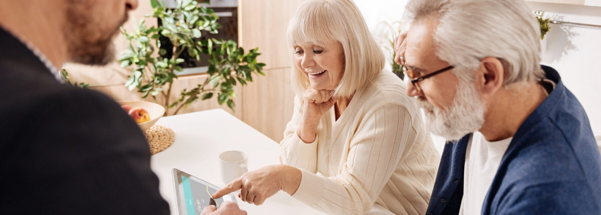 Older couple smiling and looking at a smart device