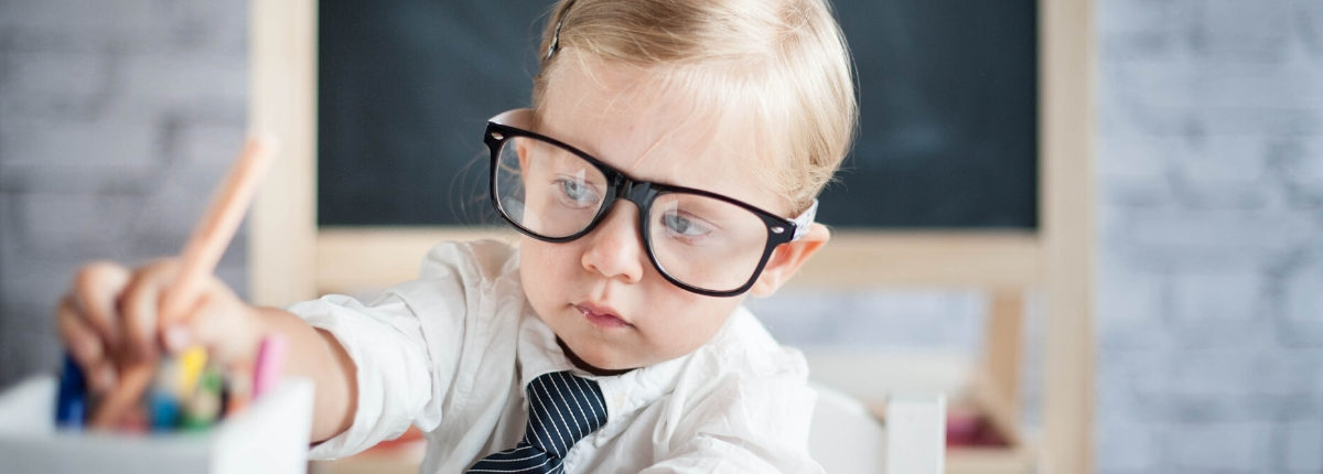 A small child with oversized glasses coloring in a classroom setting