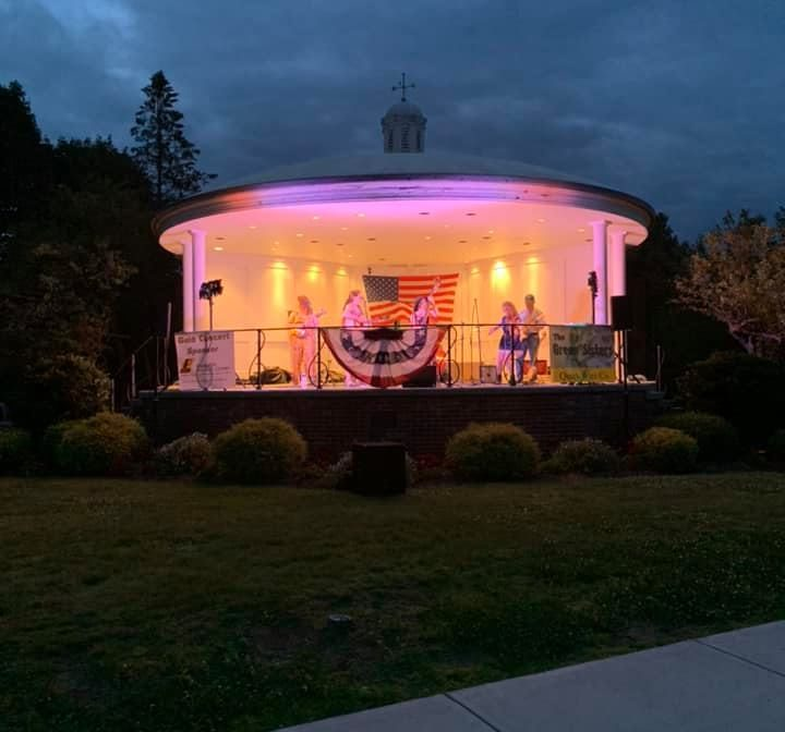West Brookfield Common bandstand at night, lit up with warm lights beneath a dark blue sky.