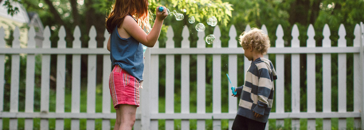 Children blowing bubbles by a white picket fence.